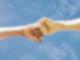 Zwei Hände werden gefaustet. Im Hintergrund blauer Himmel
